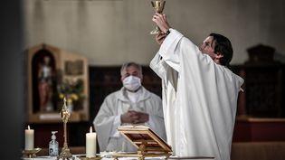 Un prêtre célèbre une messe à l'église Saint-Jean-Baptiste de Neuilly-sur-Seine (Hauts-de-Seine), le 23 mai 2020, au premier jour de la reprise des cérémonies religieuses. (STEPHANE DE SAKUTIN / AFP)