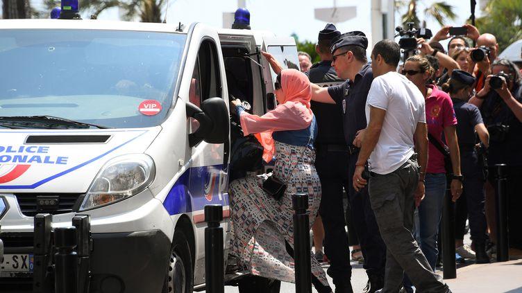 Des policiers arrêtent une femme le 26 mai 2017 à Cannes (Alpes-Maritimes), à l'occasion d'une baignade collective en burkini. (ANNE-CHRISTINE POUJOULAT / AFP)