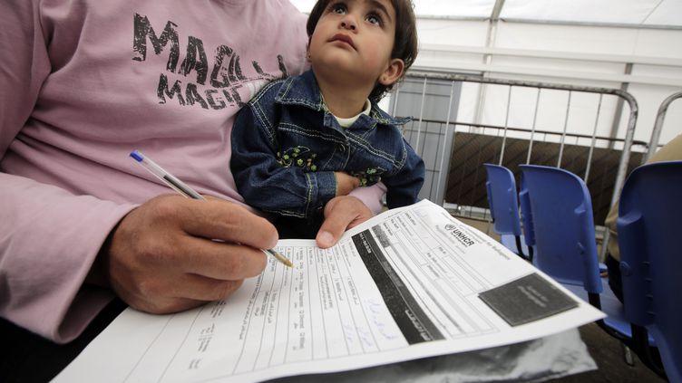 Un réfugié syrien, accompagné de son enfant,remplit des documents du Haut Commissariat des Nations unies pour les réfugiés, le 3 avril 2014, à Tripoli (Liban). (JOSEPH EID / AFP)