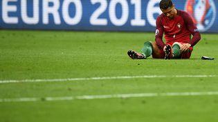 Cristiano Ronaldo, blessé, sur le terrain du Stade de France, lors de la finale de l'Euro, le 10 juillet 2016. (FRANCK FIFE / AFP)