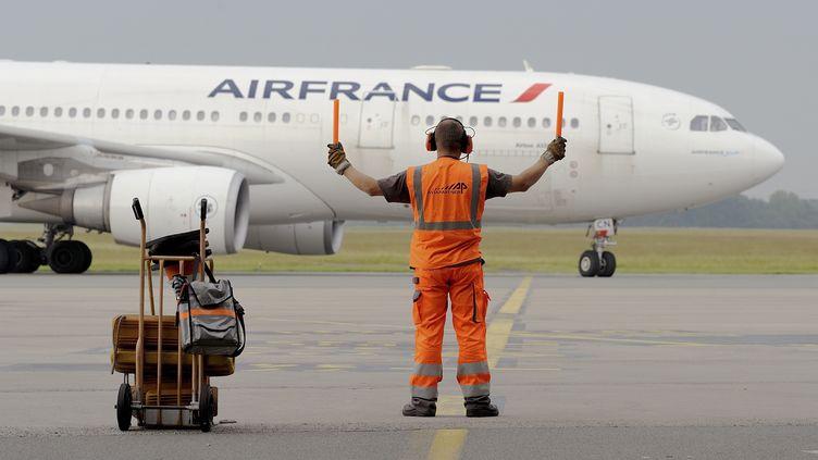 Un guide de piste oriente un avion d'Air France, le 9 juin 2014, à l'aéroport de Lille. (DENIS CHARLET / AFP)