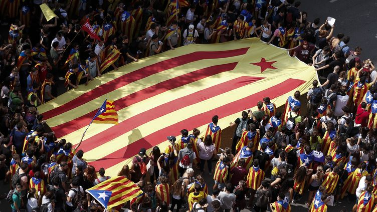 Des étudiants manifestent avec un drapeau catalan pro-indépendance géant, à Barcelone (Espagne), le 28 septembre 2017, lors d'une manifestation en faveur du référendum d'autodétermination. (PAU BARRENA / AFP)