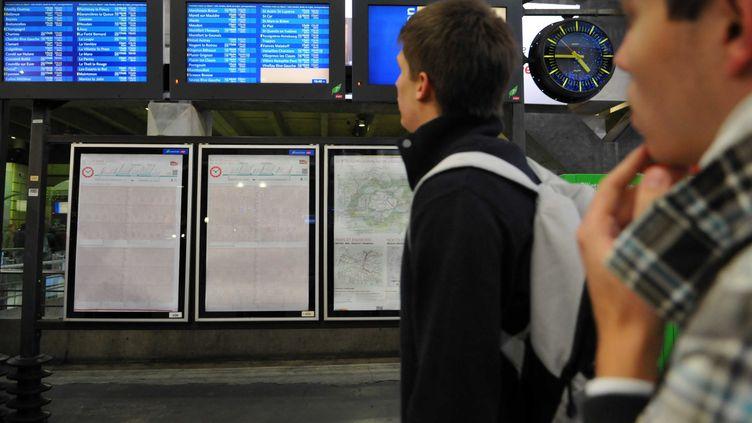 Des voyageurs consultent les horaires des trains à Paris, en décembre 2011. (DURAND FLORENCE / SIPA)