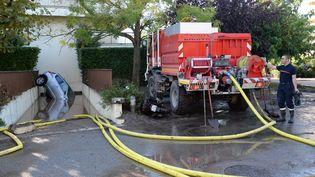 Les pompiers drainent l'entrée d'un garage pour récupérer un véhicule, à Mandelieu-la-Napoule. (BORIS HORVAT / AFP)