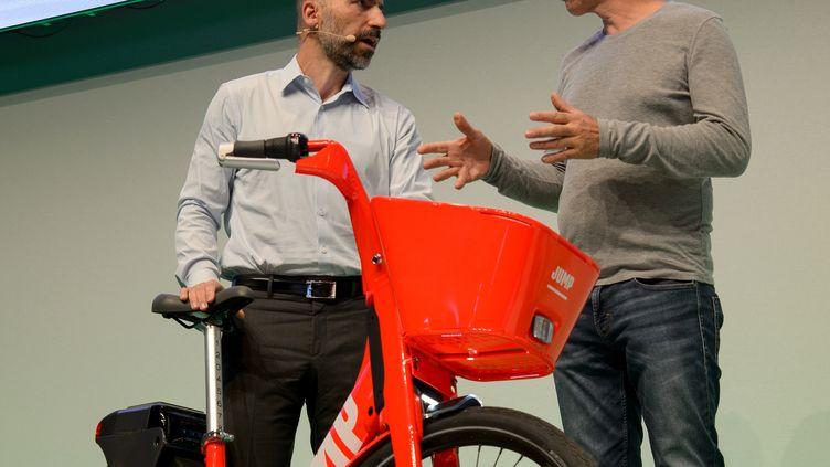 Le patron d'Uber,Dara Khosrowshahi (à gauche), présente le vélo de sa compagnie, à Berlin (Allemagne), lors de la conférence NOAH, le 6 juin 2018. (SINA SCHULDT / DPA)