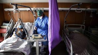 Une infirmière au chevet d'un patient positif au Covid-19, le 22 octobre 2020 à Gonesse (Val-d'Oise). (CHRISTOPHE ARCHAMBAULT / AFP)