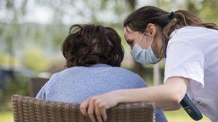 Une employée d'un Ehpad s'occupe d'une résidente, à Thise (Doubs), le 16 avril 2020. (SEBASTIEN BOZON / AFP)