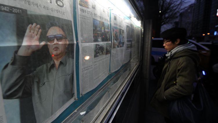 Un homme lit un journal au sujet de la mort de Kim Jong-il, à Séoul (Corée du Sud), le 20 décembre 2011. (PRAKASH SINGH /AFP PHOTO)