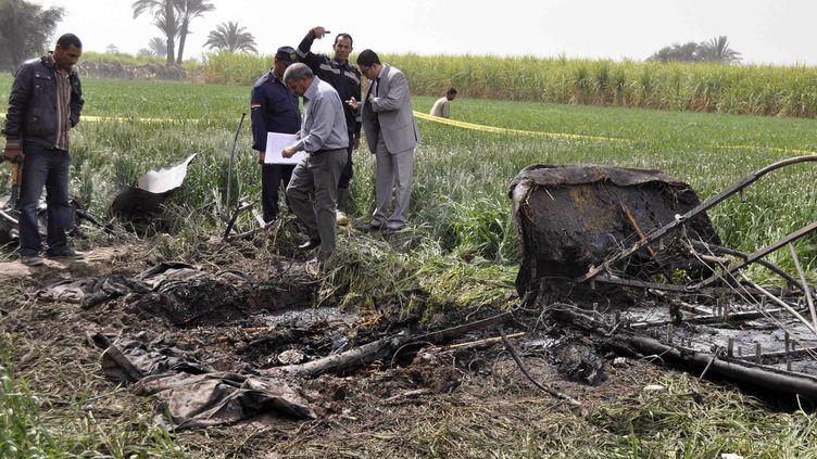 Des enquêteurs égyptiens inspectent la carcasse de la montgolfière qui a explosé puis s'est écrasée à Louxor (Egypte) le 26 février 2013, provoquant la mort d'au moins 19 personnes. (STR / AFP)