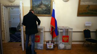 Un homme glisse un bulletin dans l'urne, le 18 mars 2018, à l'ambassade russe à Londres (Royaume-Uni). (HANNAH MCKAY / REUTERS)