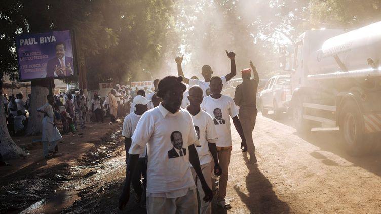 Des partisans du président camerounais Paul Biya marchent dans une rue de la ville, après sa réunion électorale, le 29 septembre 2018. C'était la première fois depuis 2012 que le président se rendait dans une province. Jamais une élection camerounaise n'avait encore été préparée, alors que l'armée est déployée dans trois des dix régions du pays: l'extrême-Nord, où elle combat les djihadistes de Boko Haram, et les deux régions anglophones du Nord-Ouest et du Sud-Ouest, où des séparatistes armés réclament l'indépendance. Huit candidats espèrent renverser par les urnes celui qu'on appelle au Cameroun le «Sphinx». Contrairement aux trois dernières élections où l'opposant de toujours, Ni John Fru Ndi, était le principal challenger, le scrutin semble en 2018 plus ouvert. «C'est la première fois dans l'histoire du Cameroun qu'il y a des candidats d'opposition aussi démarqués, qui ont de vraies offres politiques chacune différente», estime Fred Eboko, politologue camerounais à l'Institut de recherche et développement. Paul Biya est àla tête de l'Etat camerounais depuis 1982. (ALEXIS HUGUET / AFP)