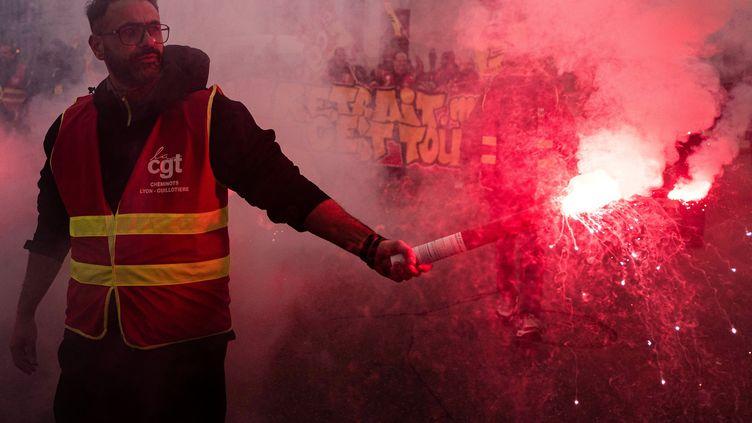 Un manifestant portant un gilet de la CGT avec un fumigène dans le cortège à Lyon (Rhône) vendredi 24 janvier 2020. (ROMAIN LAFABREGUE / AFP)