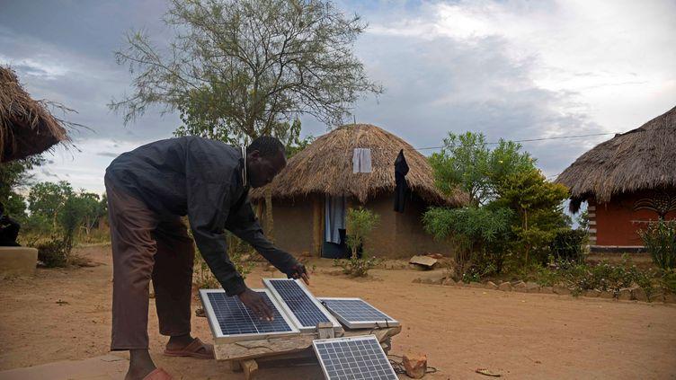Un homme installe un kit solaire pour recharger des appareils électriques dans le village de Soroti en Ouganda.  (ISAAC KASAMANI / AFP)