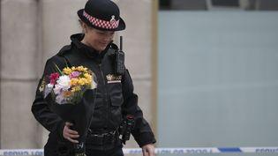 Unepolicière dépose un bouquet de fleurs près du London Bridge, le 4 juin 2017, au lendemain de l'attentat de Londres. (DANIEL LEAL-OLIVAS / AFP)