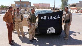 Des combattants kurdes posent avec un drapeau de l'Etat islamique dont ils se sont emparé à Makmur, en Irak, le 12 septembre 2014. (THOMAS RASSLOFF / DPA / AFP)