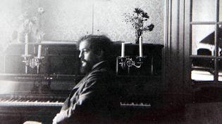 Claude Debussy assis au piano, chez son ami Lucien Fontaine, en août 1898  (Collection Particuliere Tropmi / Manuel Cohen / AFP)
