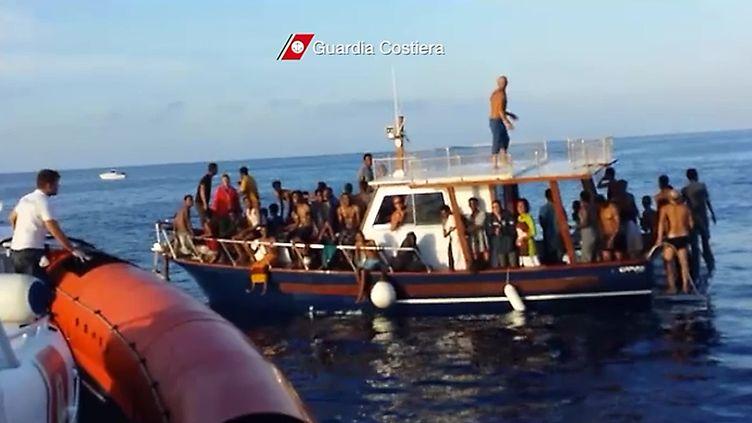 Capture d'écran d'une vidéo des gardes côtes de Lampedusa (Italie), à l'arrivée d'un bateau de migrants, le 3 octobre 2013. (GUARDIA COSTIERA / AFP)