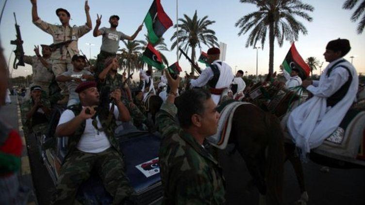 Des combattants du CNT acclament des membres de la tribu Warfalla, à Tripoli, le 9 septembre 2011 (AFP/PATRICK BAZ)