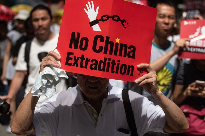 """Le slogan """"Non à l'extradition"""" est brandi dans la manifestation du 9 juin 2019, dans les rues de Hong Kong. (PHILIP FONG / AFP)"""