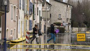 Des habitants de Tournus (Saône-et-Loire) traversent une rue inondée par la crue de la Saône, le 29 janvier 2018. (PHILIPPE DESMAZES / AFP)