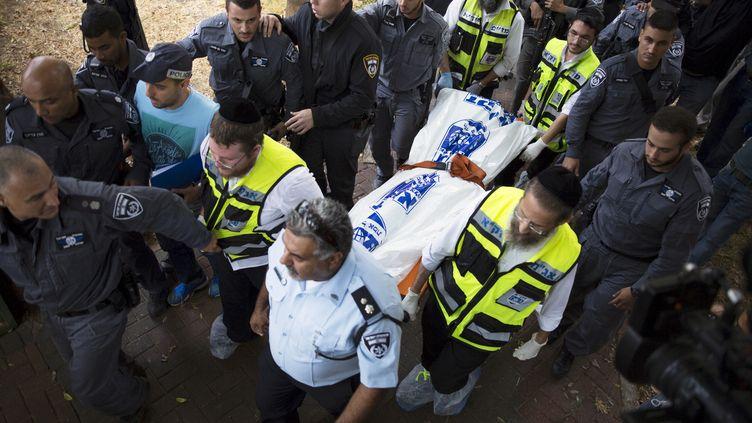 Des policiers israéliens transportent le corps du Palestinien ayant attaqué un soldat à Kiryat Gat, le 7 octobre 2015. (AMIR COHEN / REUTERS)