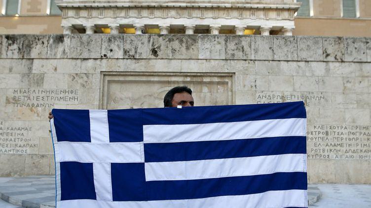 Un manifestant brandit un drapeau grec devant le bâtiment du Parlement, à Athènes (Grèce), le 13 juillet 2015. (JEAN-PAUL PELISSIER / REUTERS)