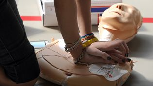 Une personne s'entraîne à la pratique du massage cardiaque sur un mannequin, lors d'une formation aux gestes de premiers secours, le 9 avril 2011 àAmmerschwihr (Haut-Rhin). (PATRICK HERTZOG / AFP)