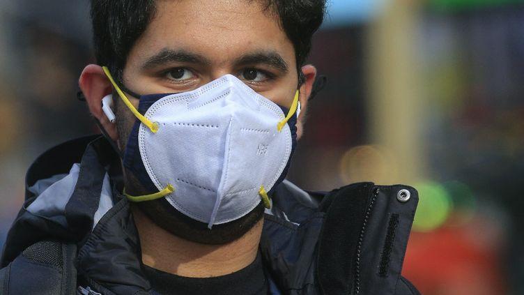 Un homme porte un masque chirurgical par-dessus un masque en tissu, le 10 décembre 2020 à Times Square, à New York (Etats-Unis). (KENA BETANCUR / AFP)