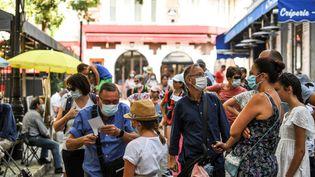 Des passants portent un masque à Montmartre à Paris, le 11 août 2020. (ALAIN JOCARD / AFP)