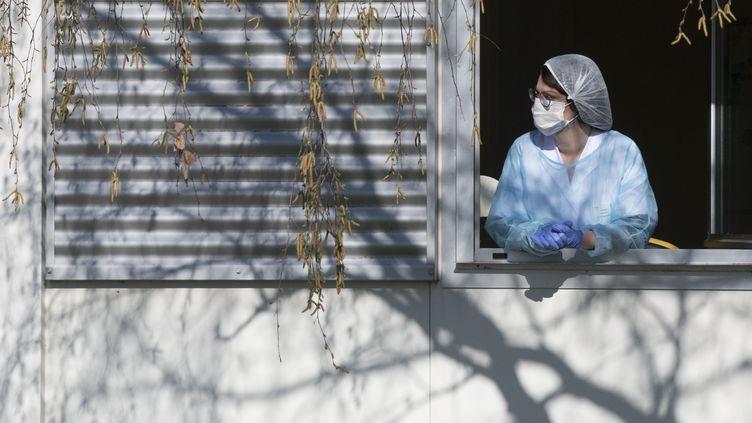 Une soignante à la fenêtre de l'hôpital Emile Muller, à Mulhouse, le 24 mars 2020. (SEBASTIEN BOZON / AFP)