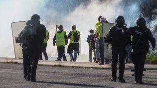 """Des """"gilets jaunes"""" et des policiers au Boulou, le 22 décembre 2018. (RAYMOND ROIG / AFP)"""
