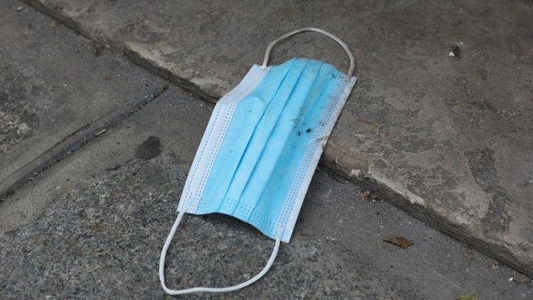 Un masque sanitaire jeté dans la rue. (AURELIE LADET / MAXPPP)