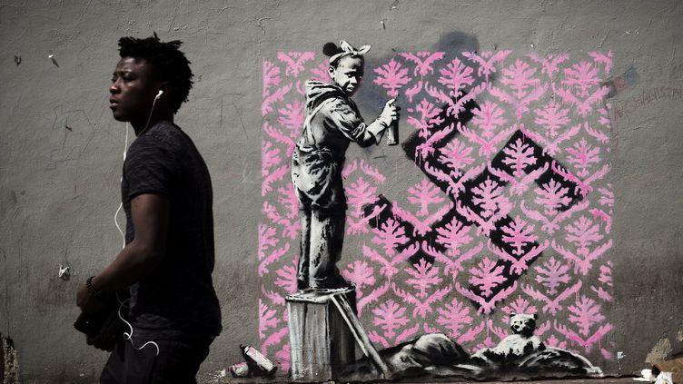 Un homme devant une œuvre attribuée au street artist Banksy, à Paris, le 24 juin 2018. (PHILIPPE LOPEZ / AFP)