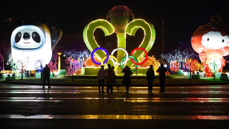 Personnes visitant un spectacle de lanternes sur le thème des Jeux Olympiques et Paralympiques d'hiver de Beijing 2022 sur la place du citoyen à Zhangjiakou, dans le nord de la province du Hebei. (STR / AFP)