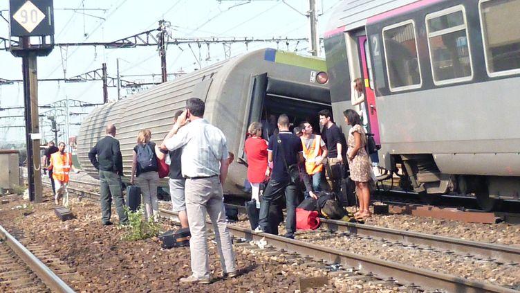 Une voiture renversée après le déraillement d'un train à Brétigny-sur-Orge (Essonne), le 13 juillet 2013. (A.-J.CASSAIGNE / AFP)