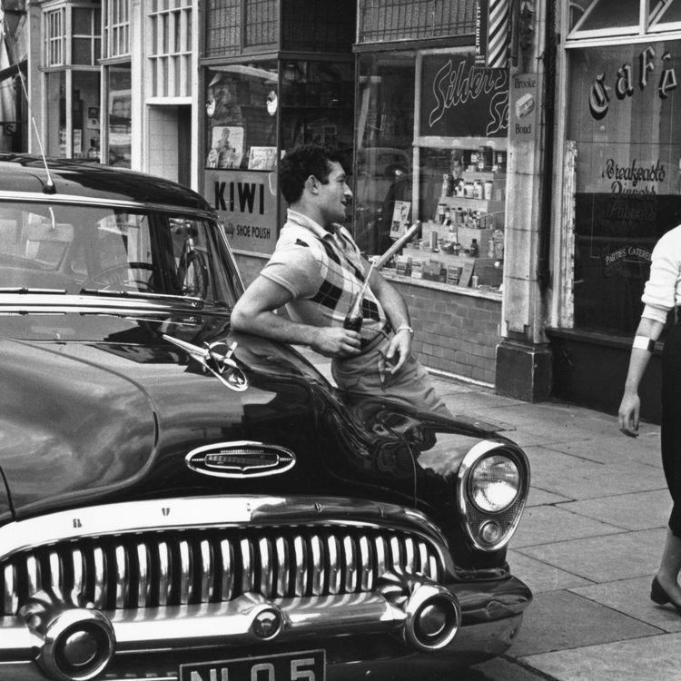Un homme interpelle une passante dans une rue américaine, le 23 octobre 1954. (CHARLES HEWITT / PICTURE POST / GETTY IMAGES)