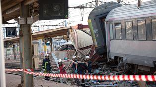 Des pompiers fouillant la carcasse du train accidenté en gare de Brétigny-sur-Orge (Essonne), le 13 juillet 2013. (ARNAULT SERRIERE / MAXPPP)