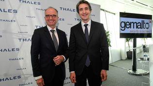 Philippe Vallee (à g.), PDG de Gemalto, et Patrice Caine, PDG de Thales, ont officialisé l'union de leur entreprise, lundi 18 décembre 2017, à Puteaux (Hauts-de-Seine). (BERTRAND GUAY / AFP)