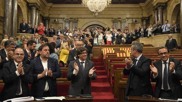 Des élus independantistes catalans applaudissent l'adoption d'une loiprévoyant un référendum d'autodétermination dans la région, mercredi 6 septembre 2017, à Barcelone (Espagne). (LLUIS GENE / AFP)