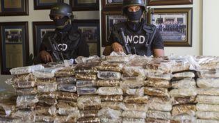 Des policiers dominicains posent devant les 680 kg de cocaïne saisie à bord du Falcon 50 des quatre Français, le 21 mars 2013. (ERIKA SANTELICES / AFP)