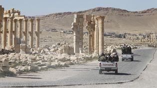 Des soldats de l'armée syrienne passent près de l'Arc de Triomphe de la cité antique de Palmyre (Syrie), le 1er avril 2016. (OMAR SANADIKI / REUTERS)