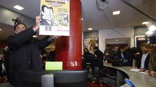 Libération accueille le 9 novembre dans ses locaux l'équipe éditoriale de Charlie Hebdo, après la tuerie du 7 novembre au journal satirique. La Une de Libération brandie date de novembre 2011. (BERTRAND GUAY / AFP)