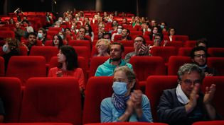 """Les spectateurs applaudissant avant la projection du film """"Les Parfums"""", lors de la réouverture des salles de cinéma, le 21 juin 2020 à Paris. (ABDULMONAM EASSA / AFP)"""