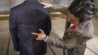 Michael Nguyen, copropriétaire de la maison de couture Garrison Bespoke, montre des impacts sur une veste pare-balles, le 5 novembre 2013. (MARK BLINCH / AP / SIPA)
