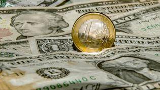Une pièce d'1 euro sur des billets en dollar. (PHILIPPE HUGUEN / AFP)