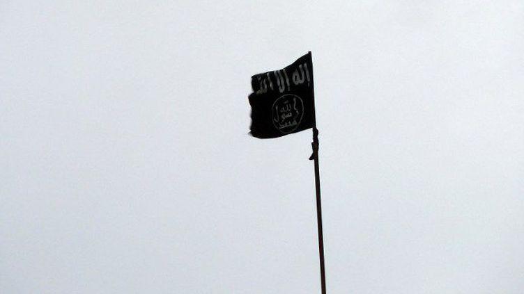 Le drapeau noir du groupe Etat islamique hissé sur l'un des bâtiments de la base Sheikh Suleiman, à 25 kilomètres au nord-ouest de la ville d'Alep, le 9 décembre 2012. (HERVE BAR / AFP)