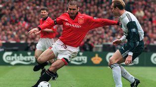 Le capitaine de Manchester United, le Français Eric Cantona dribble John Scales de Liverpoool en première mi-temps de la finale de la coupe d'Angleterre, le 11 mai 1996 sur le stade de Wembley à Londres (GERRY PENNY / AFP)