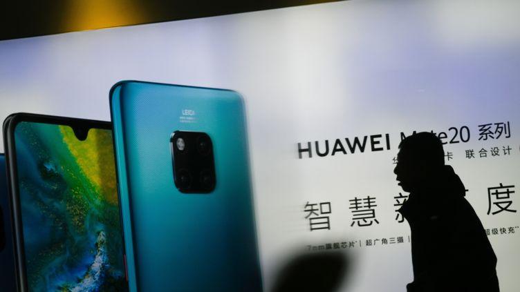 Un homme marche devant une publicité Huaweià Pékin (Chine) le 29 janvier 2019. (WANG ZHAO / AFP)