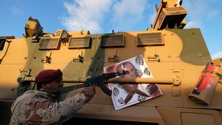 Un membre de l'ANL, la force du maréchal Haftar, pointe son arme sur une photo du président turc Tayyip Erdogan. (ESAM AL-FETORI / X02867)