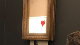 """La """"Fille au ballon"""" de Banksy, sort de son cadre, chez Sotheby's, à Londres (Royaume-Uni), le 5 octobre 2018. (SOTHEBY'S)"""